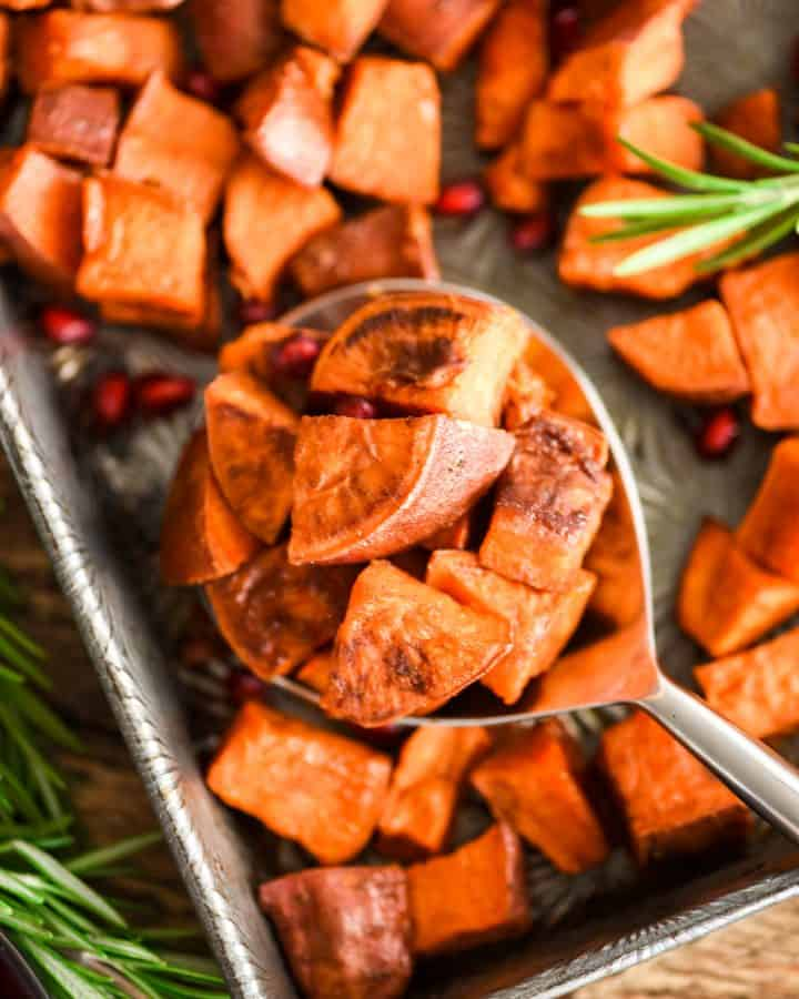 a spoon taking a scoop of Cinnamon Roasted Sweet Potatoes out of a baking dish