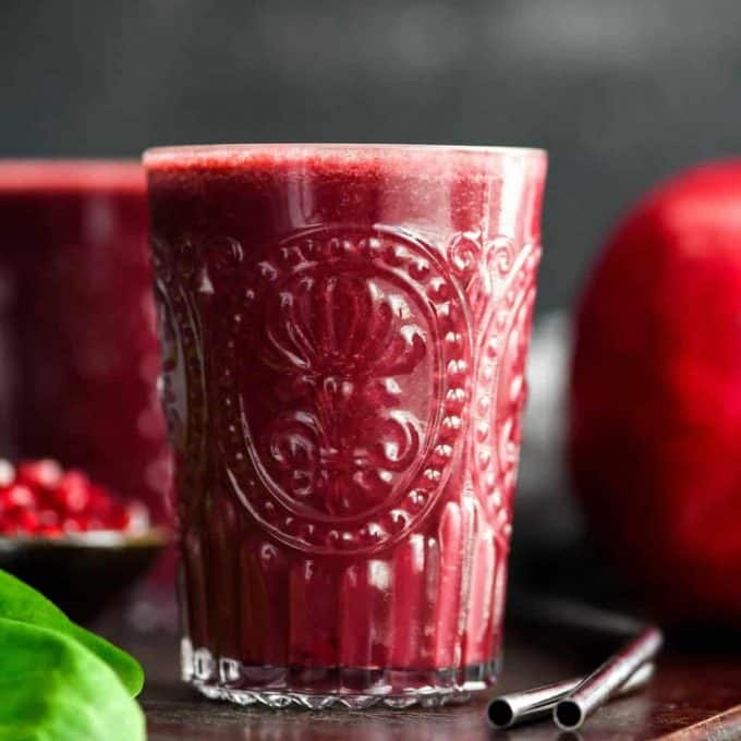 Front view of a glass filled with Beet & Pomegranate Smoothie with Spinach