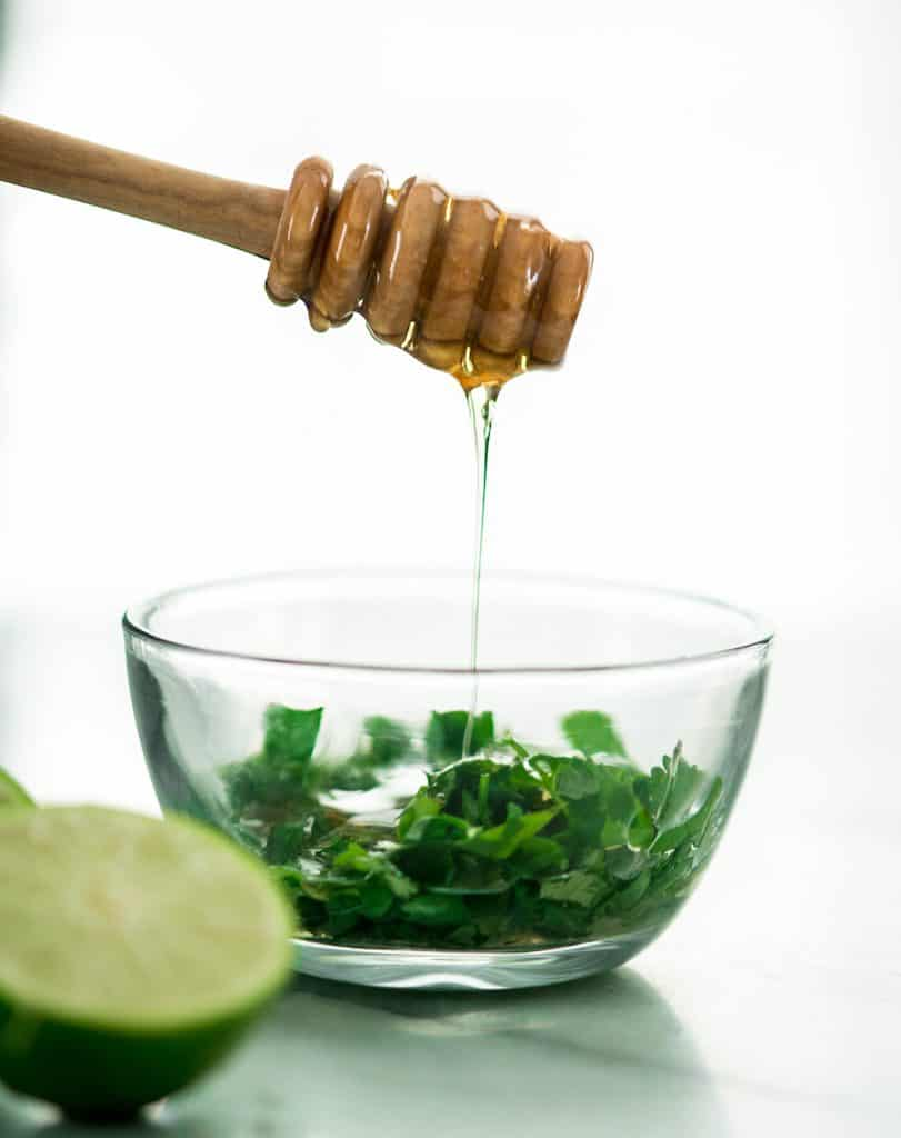 Front view of honey being drizzled into a bowl of cilantro making the sauce for Honey Lime Black Bean Sweet Potato Tacos