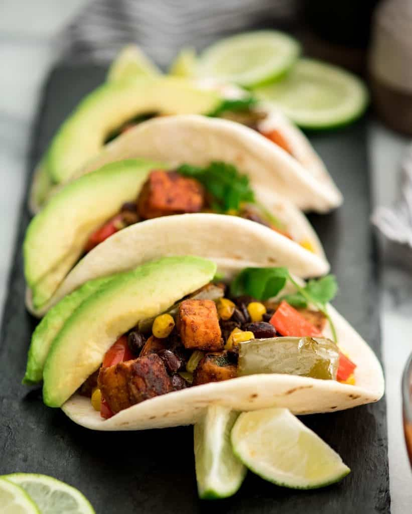 Side view of three Black Bean Sweet Potato Tacos arranged on a rectangular plate
