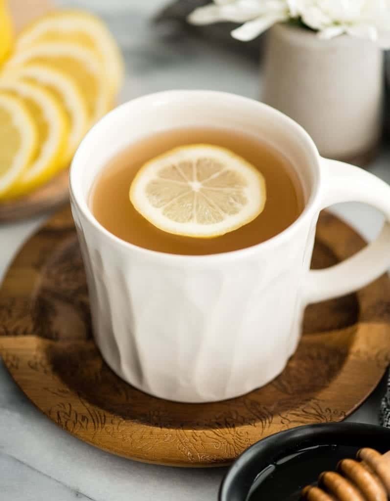 Side view of Immune Boosting Tea Recipe in a mug with a slice of lemon in it
