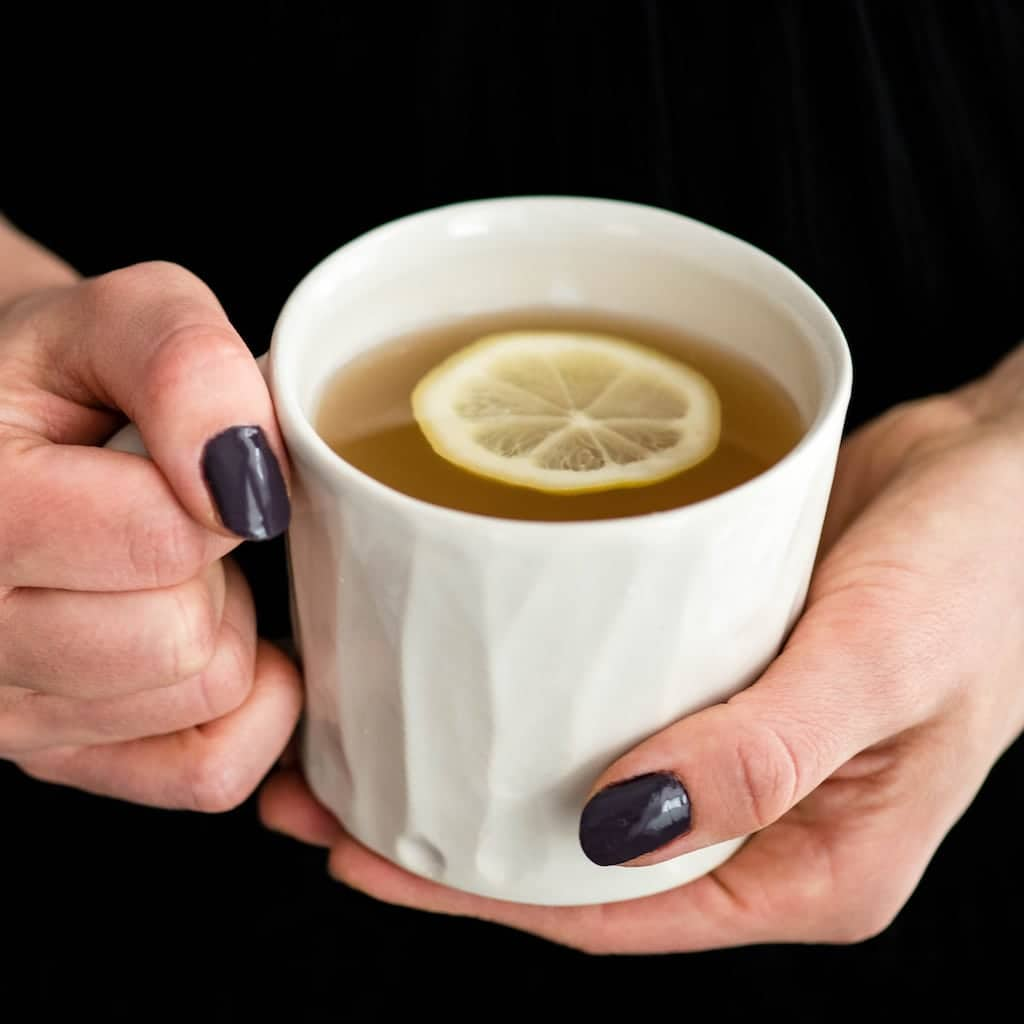 Front view of two hands holding a mug of Immune Boosting Tea Recipe with a lemon slice in it