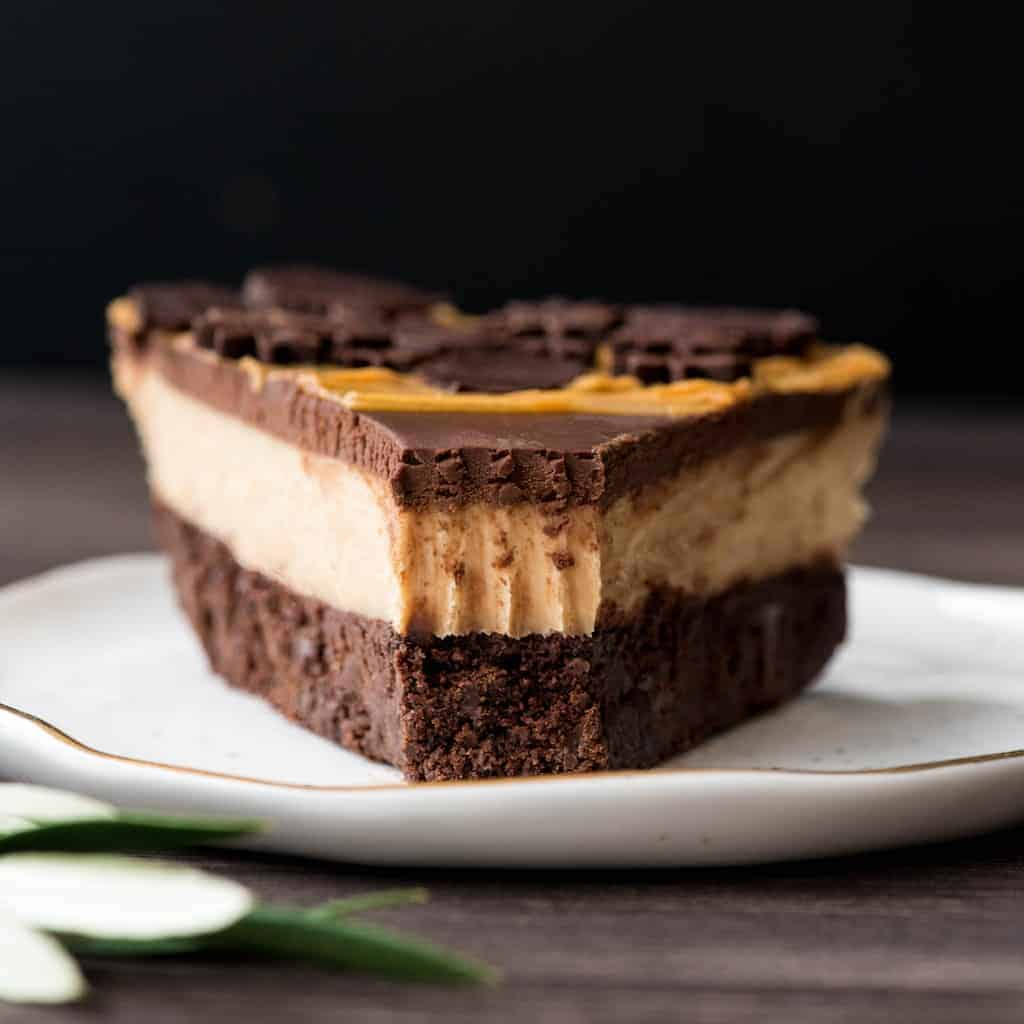 Front view of a slice of Chocolate Peanut Butter Pie recipe on a plate with a bite taken out of it