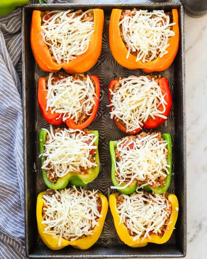 Overhead view of healthy Italian Stuffed Peppers arranged on a baking sheet with cheese sprinkled on top before baking