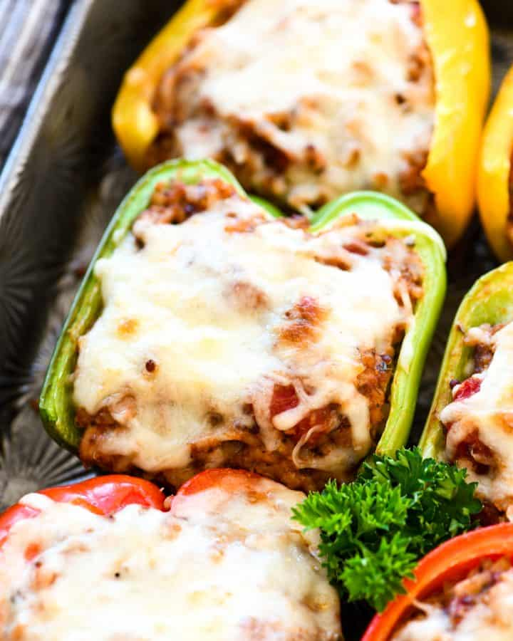 Up close side view of three healthy Stuffed Peppers on the baking sheet