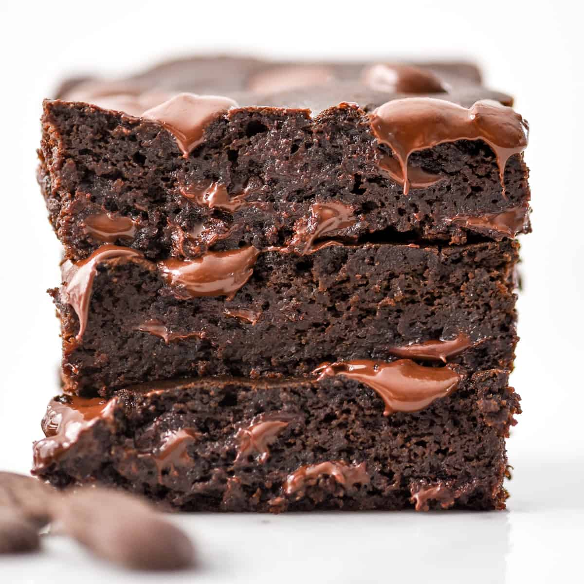 a stack of 3 black bean brownies with melty chocolate chips