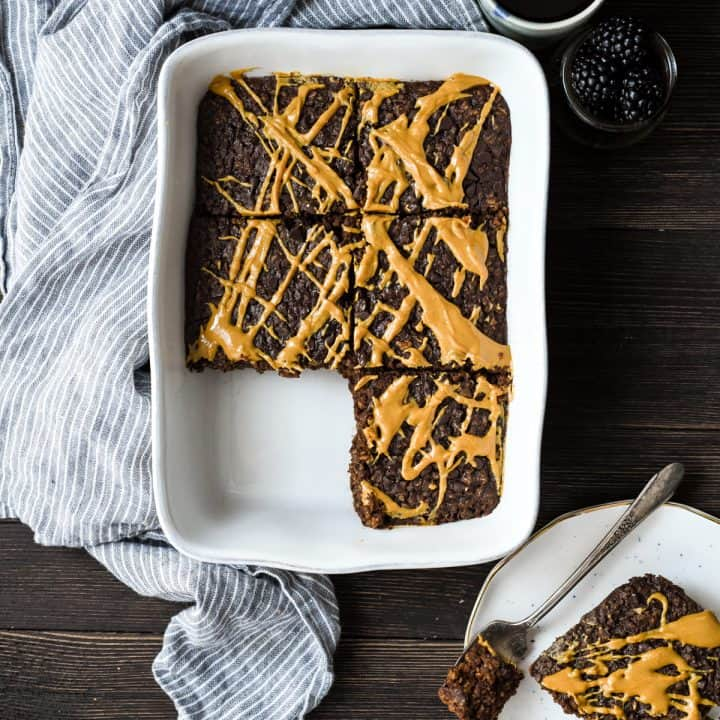 Overhead view of Healthy Chocolate Peanut Butter Baked Oatmeal cut into 6 squares with one removed on a plate next to the baking dish