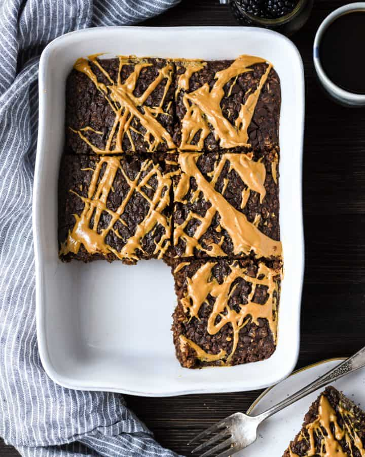Healthy Chocolate Peanut Butter Baked Oatmeal in a baking pan with 1 piece cut out of it