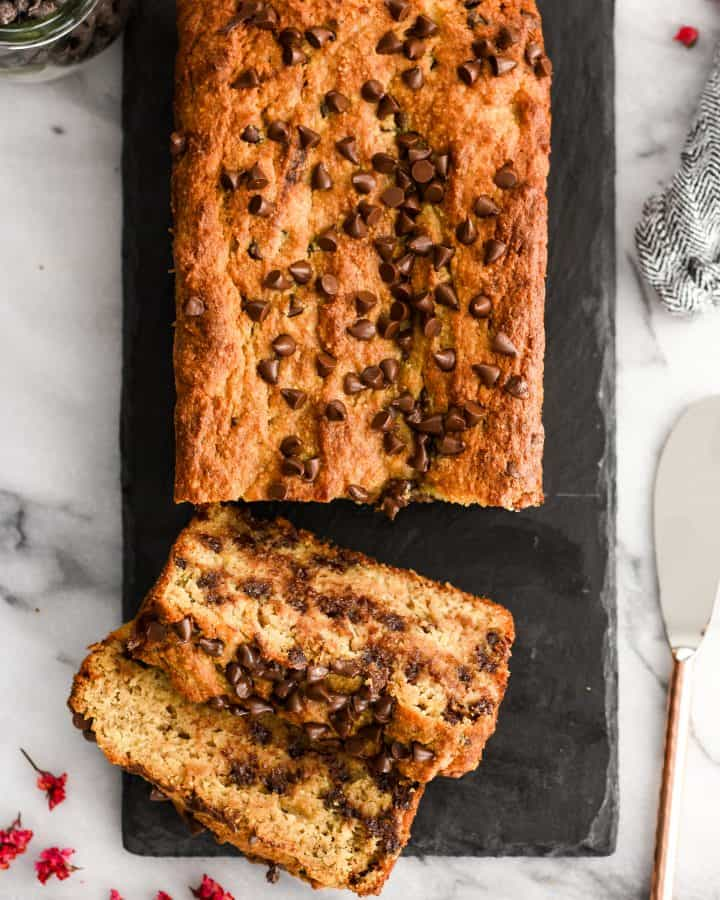 Overhead view of a loaf of paleo banana bread with two slices cut and laying on each other