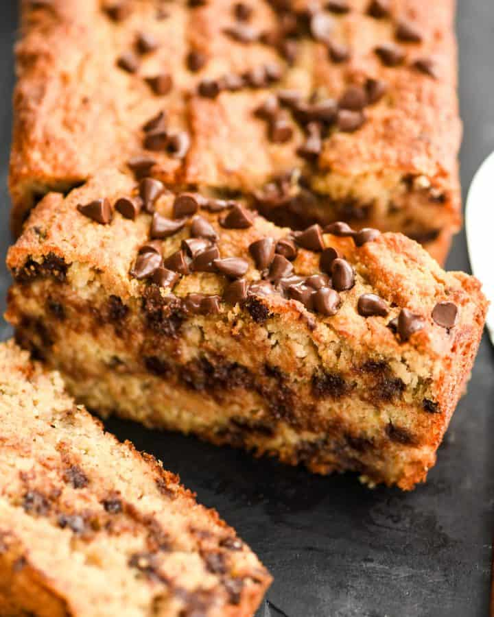 Up close overhead shot of one slice of paleo banana bread with the loaf in the background