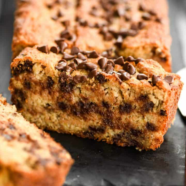 up close photo of a piece of paleo banana bread standing up near the loaf.