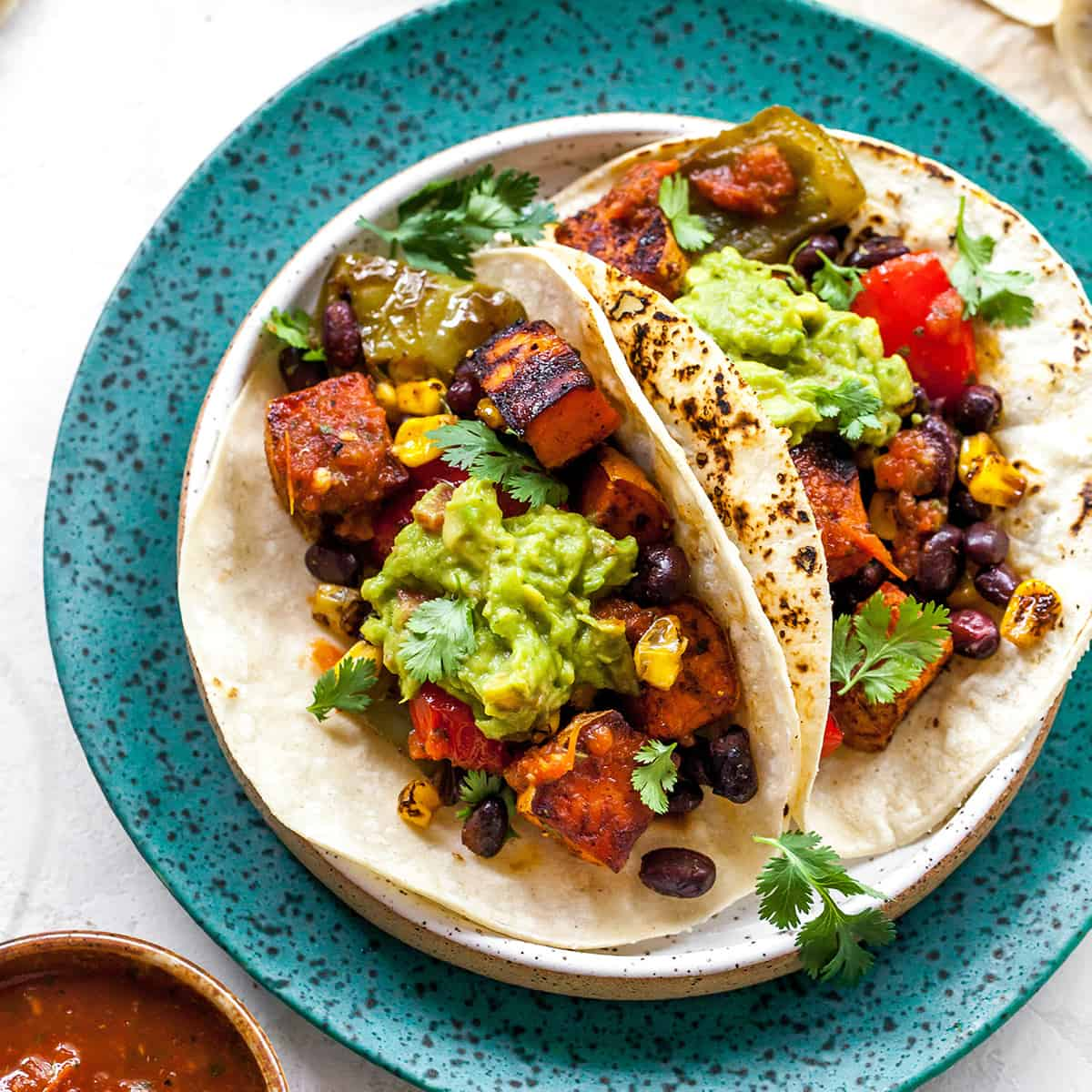 overhead view of three black bean sweet potato tacos with guacamole on a plate