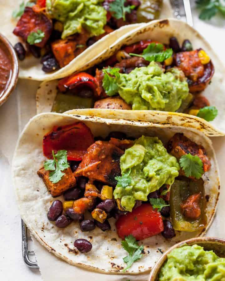 overhead view of three black bean sweet potato tacos with guacamole