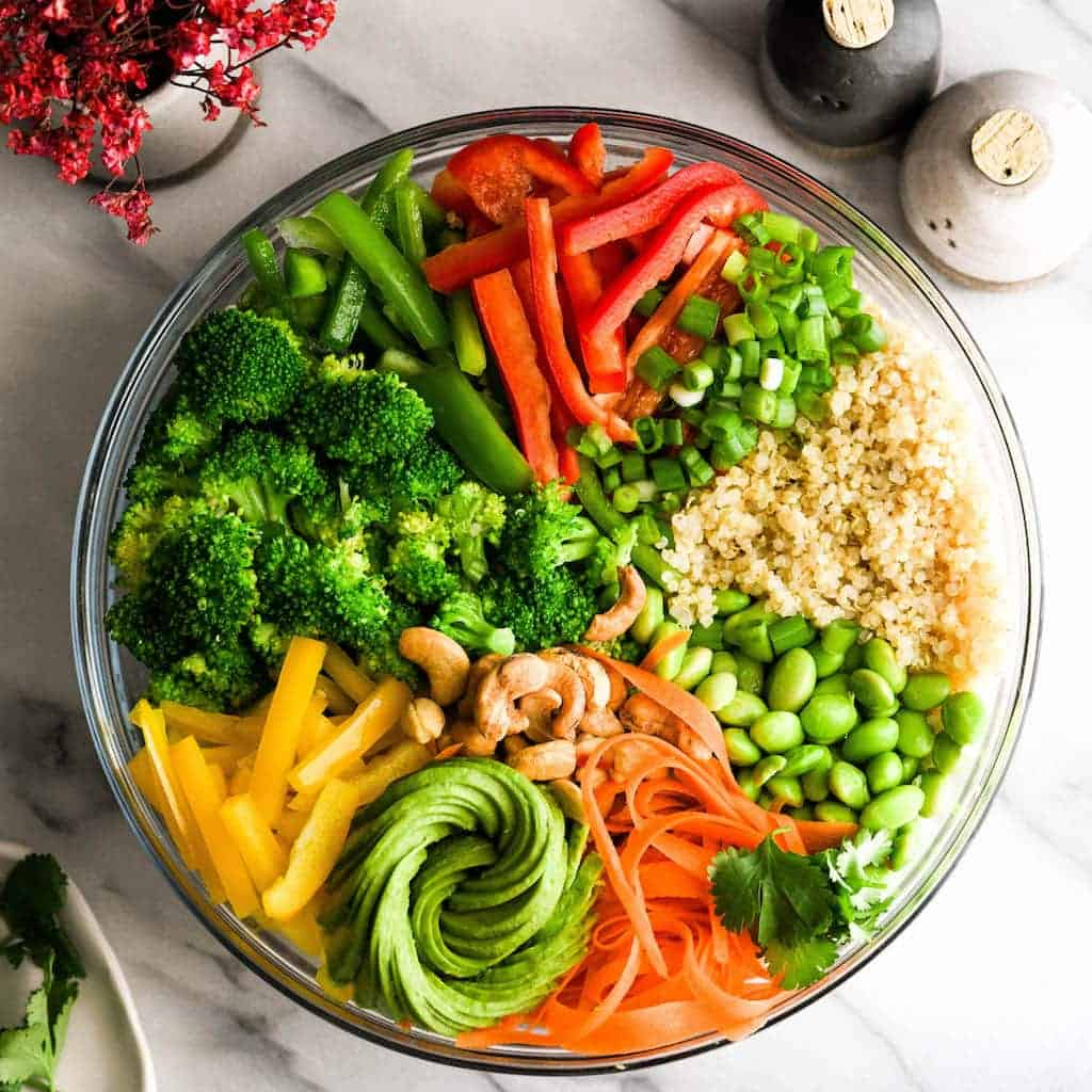 Overhead view of a large bowl with all the ingredients of Asian Quinoa Salad with Peanut Dressing recipe arranged in a pretty design with an avocado rose