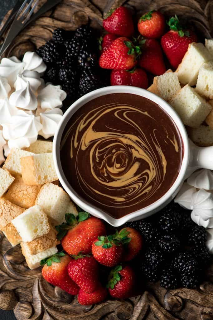 Overhead view of Dairy-Free Chocolate Peanut Butter Fondue with a peanut butter swirl on a wooden platter surrounded by angel food cake, blackberries, strawberries and merengues