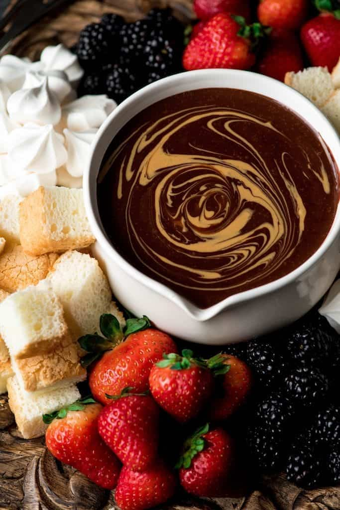 Side view of Dairy-Free Chocolate Peanut Butter Fondue with a peanut butter swirl on a wooden platter surrounded by angel food cake, blackberries, strawberries and merengues
