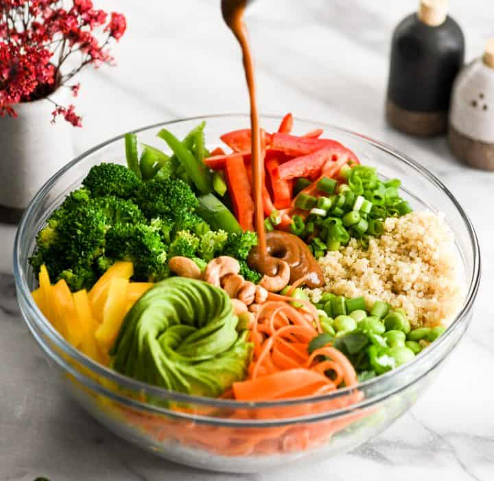 Side view of Peanut sauce being poured into a bowl with all the ingredients of asian quinoa salad with peanut dressing recipe