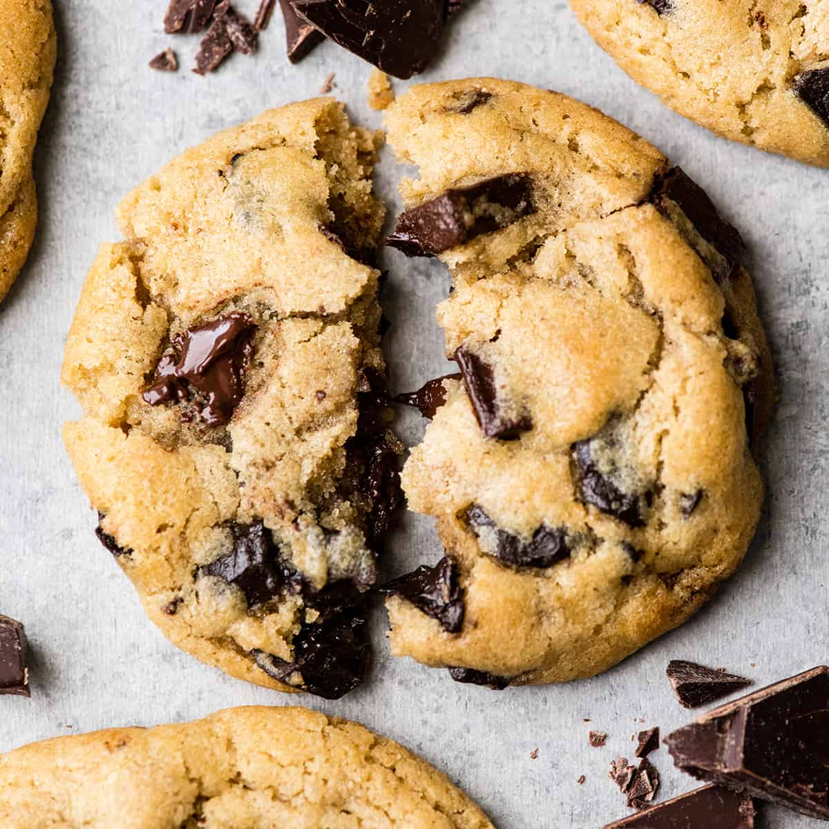 Overhead view of one chocolate chip cookie torn in half with melty chocolate chips surrounded by three other cookies and chopped chocolate