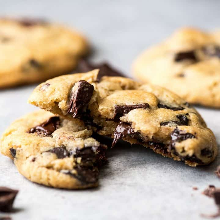Front view of a chocolate chip cookie cut in half with melty chocolate chips