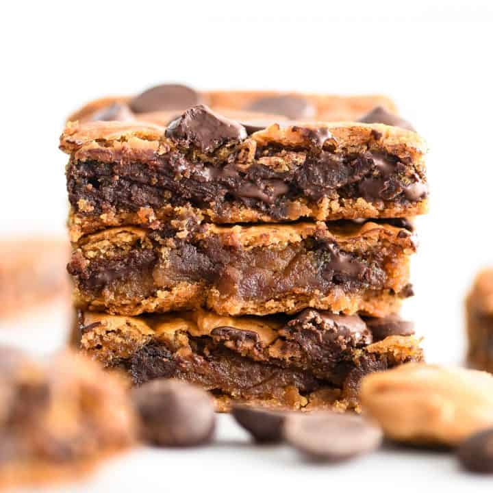 a stack of three healthy peanut butter chickpea blondies with melty chocolate fresh from the oven
