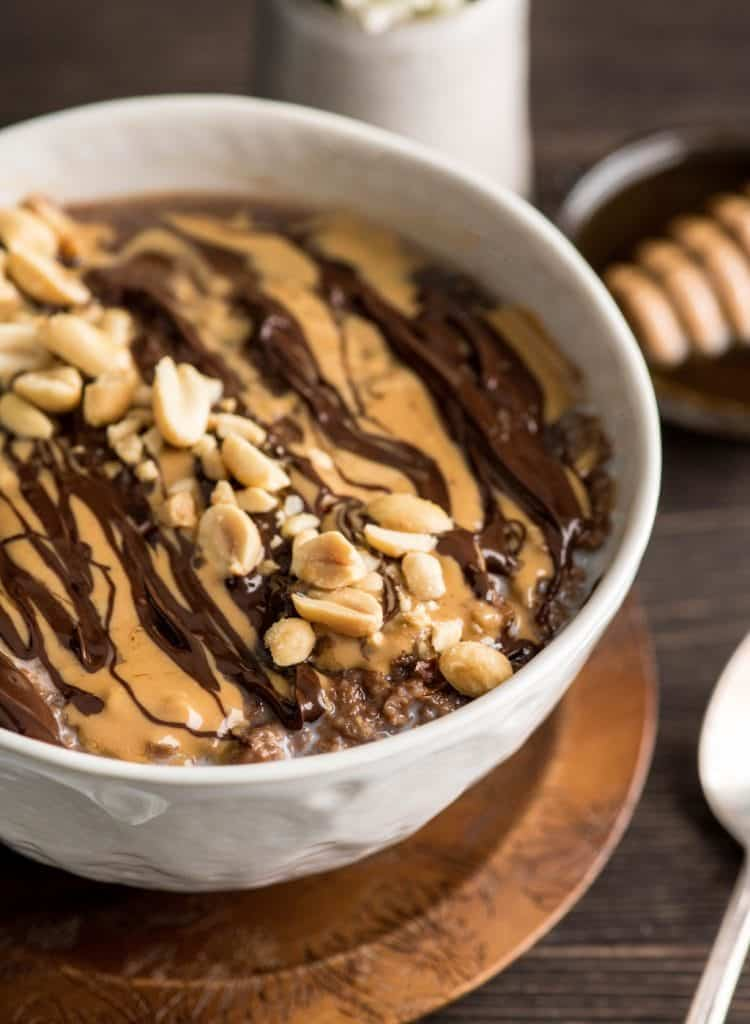 Overhead view of a bowl of chocolate peanut butter oat bran with swirls of peanut butter and chocolate and crushed peanuts