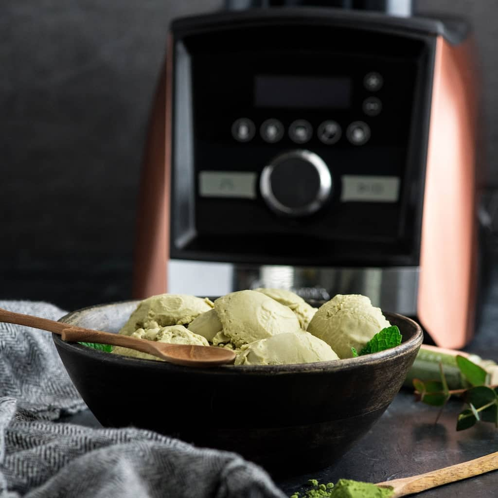 front view of a bowl of dairy-free matcha ice cream with a wooden spoon and a copper A3500 Vitamix blender in the background