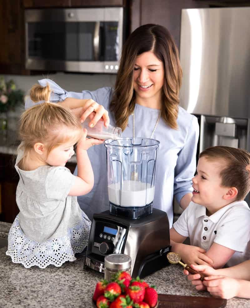 Front view of a mom helping her daughter pour almond milk into a vitamix A3500 blender making homemade chia pudding finger paints