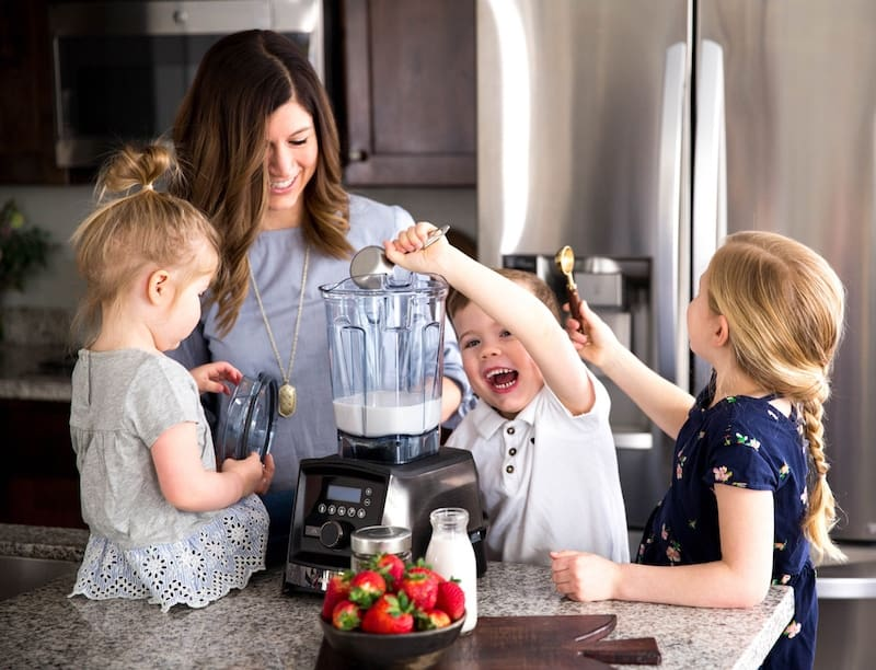 Front view of a mom with her three kids making Homemade Chia Pudding Finger Paint in a Vitamix Blender