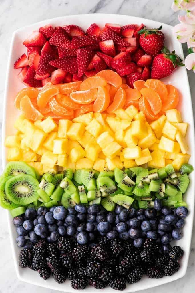 Overhead view of a large oval platter with a rainbow of fruits lined up by color