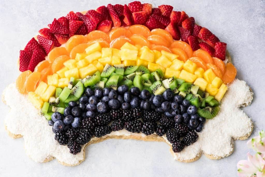 overhead view of a beautiful rainbow fruit pizza recipe in the shape of a rainbow with coconut clouds