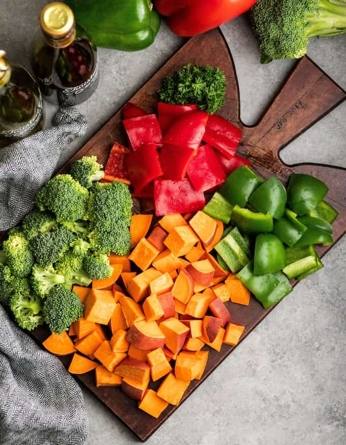 Overhead view of raw, cut up broccoli, sweet potatoes, red & green bell peppers on a cutting board surrounded by bottles of olive oil and balsamic vinegar