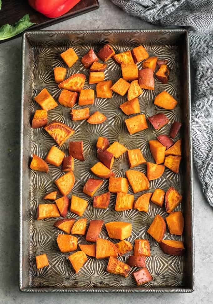 Overhead view of slightly roasted sweet potatoes in the baking pan