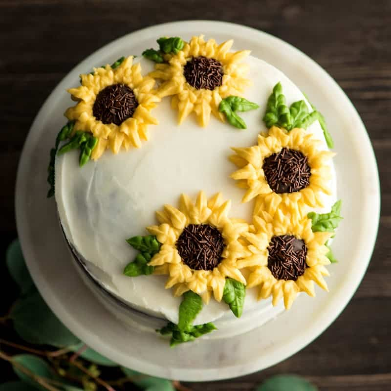 overhead view of a sunflower cake decorated with the best homemade vanilla frosting recipe