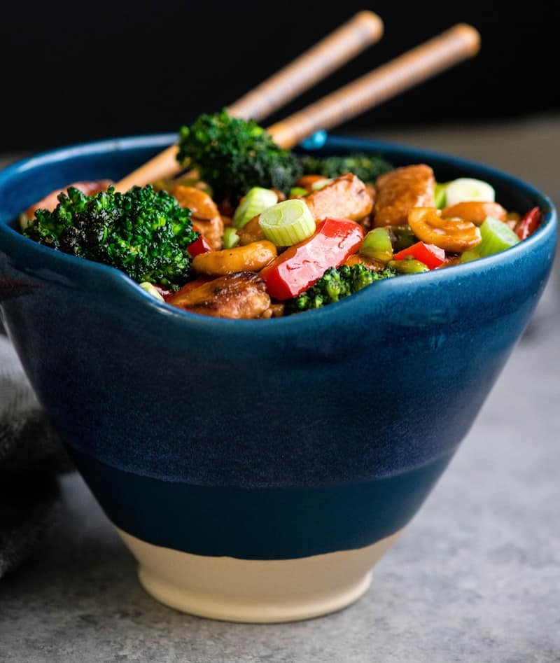 Side view of Cashew Chicken Stir Fry Recipe in a blue bowl with chopsticks