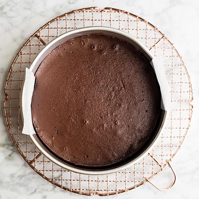 overhead view of flourless chocolate cake on a cooling rack