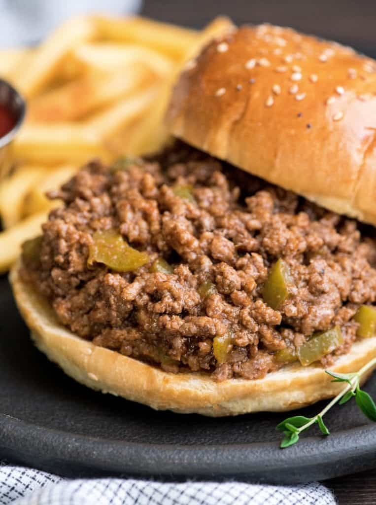 Up close front shot of healthy sloppy joes recipe on a bun with the top of the bun off to the side and french fries in the background