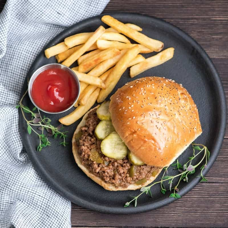 Overhead view of healthy sloppy joes recipe on a bun with pickles on a round black plate with ketchup and french fries and fresh thyme