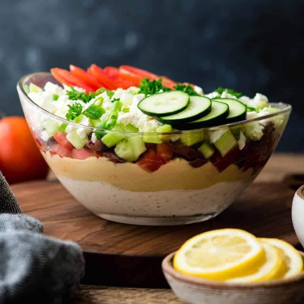 Front view of Layered Greek Dip recipe in a glass bowl on a walnut cutting board