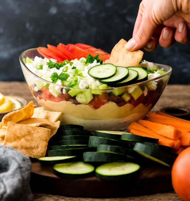 Front view of a hand dipping a pita chip into a glass bowl of Layered Greek Dip recipe on a walnut cutting board surrounded by cucumbers, carrots, and pita chips for dipping