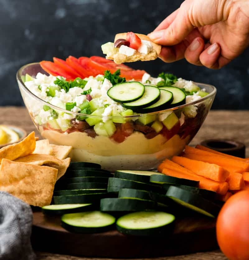Front view of a hand holding a pita chip with a dip of Layered Greek Dip recipe on a walnut cutting board surrounded by cucumbers, carrots, and pita chips for dipping