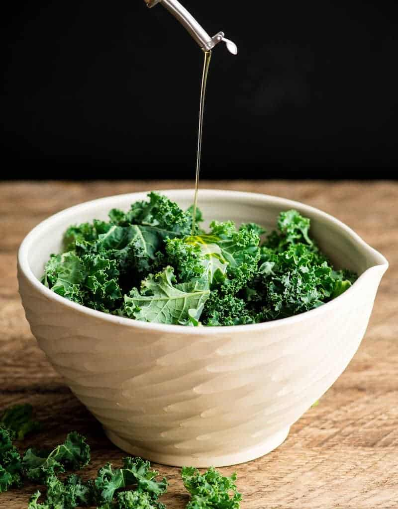 Front view of olive oil being poured into a bowl of chopped kale leaves making baked kale chips