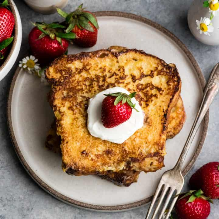 overhead view of two pieces of french toast on a plate with whipped cream and strawberries
