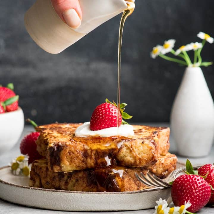 two pieces of french toast on a plate with whipped cream and strawberries and syrup being poured on top