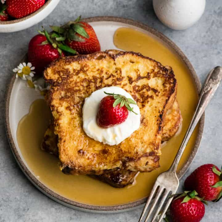 two pieces of french toast on a plate with whipped cream and strawberries and syrup