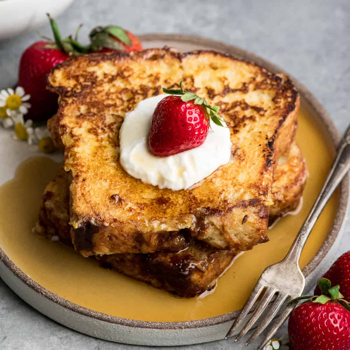 front view of two pieces of french toast on a plate with whipped cream and syrup
