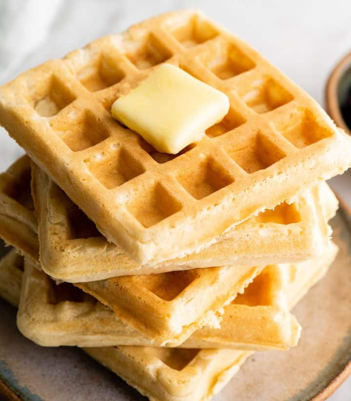 front view of a stack fo five waffles with butter on top