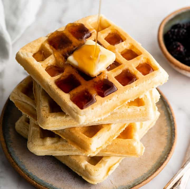 stack of 5 waffles with butter and syrup