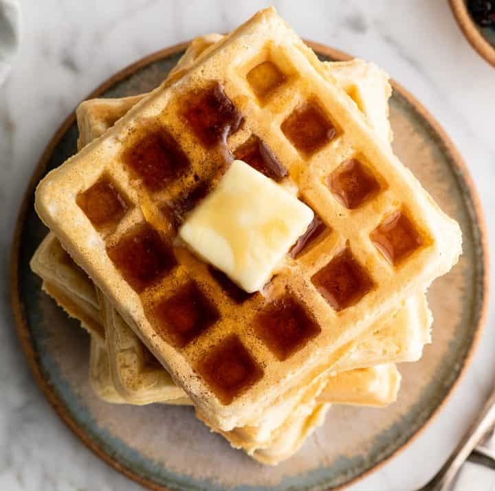 Overhead view of homemade waffle with butter and syrup