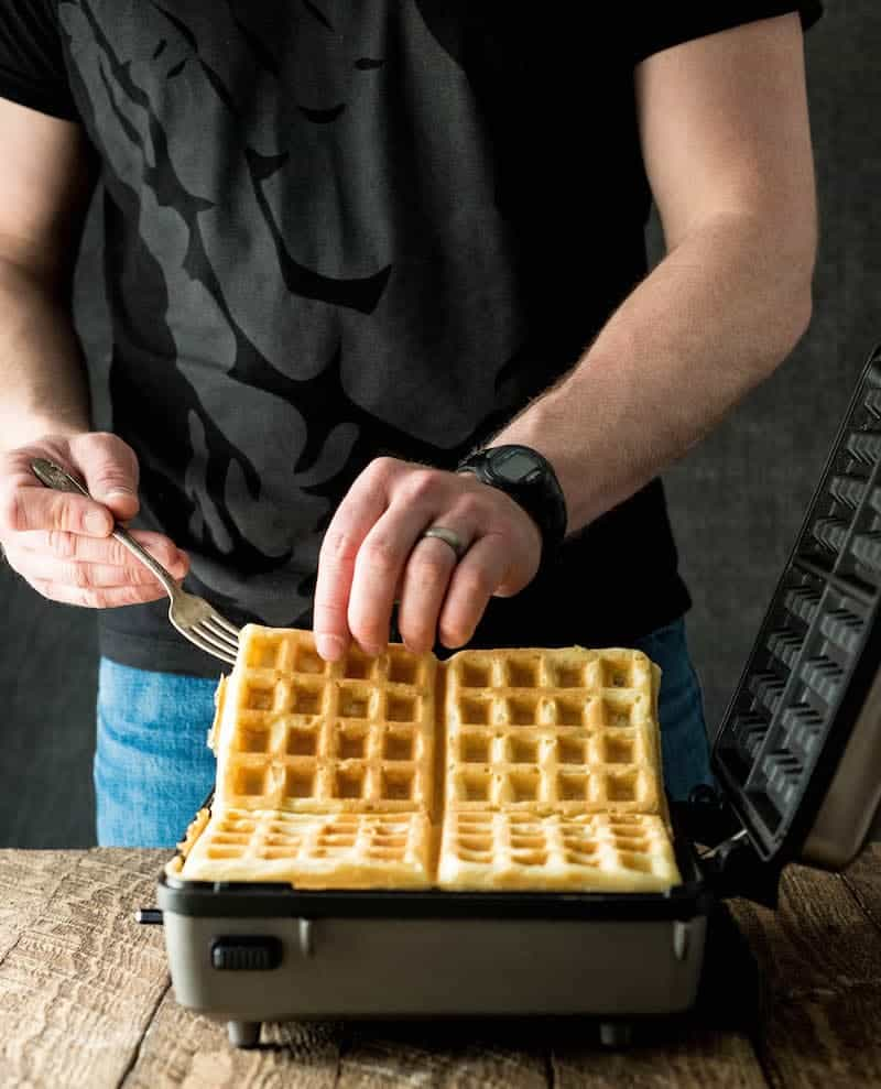 Two hands removing four Best Waffles Recipe waffles from the waffle maker after they have finished cooking