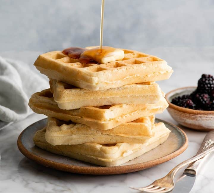 front view of syrup pouring on a stack of five homemade waffles